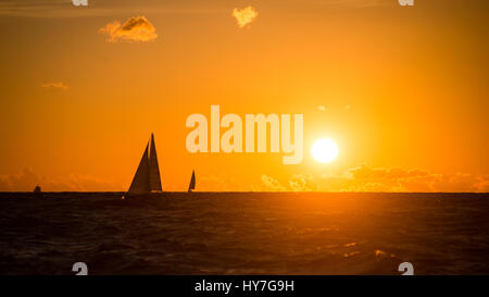 colorful orange sunrise over the lake in summer with small boat - Stockfoto