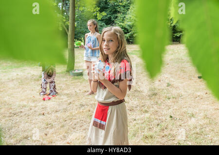 Young children play games outside in the sunshine - Stock Photo
