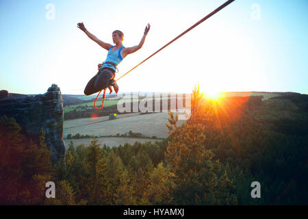 OSTROV, CZECH REPUBLIC: A female slackliner shows off on the high-wire. FROM DRESSING-UP in costume to hire-wire - Stock Photo
