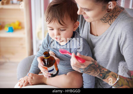 Close up of toddler taking medicine - Stock Photo