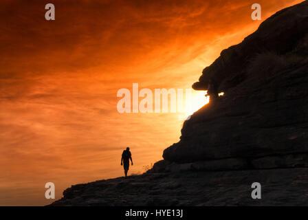 Silhouette of hiker climbing towards sunset with orange glowing sky. Northern Territories, Australia - Stock Photo