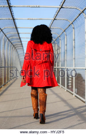 Woman In Trench Coat And Red Rain Boots Holding A Red Umbrella And