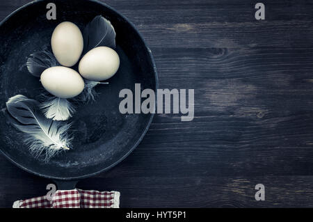 Raw eggs in a black frying pan, top view, empty space on the right - Stock Photo