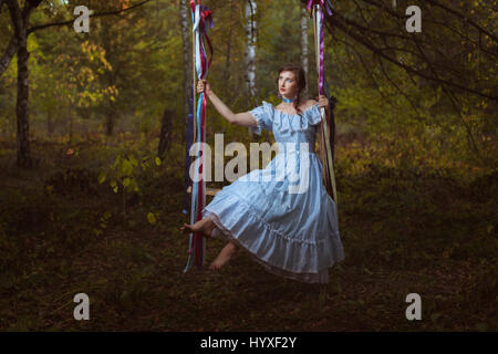 Girl swinging on a swing in the woods, her vintage retro dress. - Stock Photo