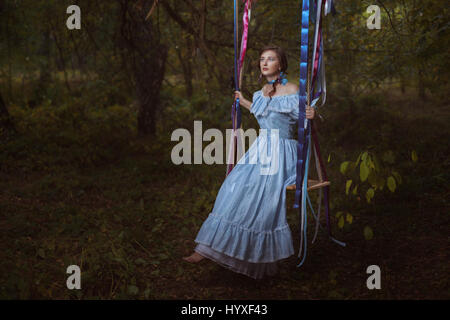 Fabulous retro woman in a smart dress in the woods sitting on a swing. - Stock Photo