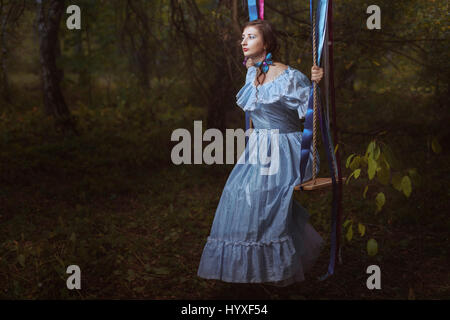 Young girl in fairy forest on the swing, she retro, vintage dress. - Stock Photo