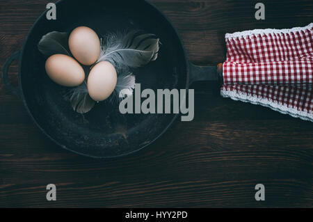 Chicken eggs in a black cast-iron frying pan on a brown wooden surface, top view - Stock Photo