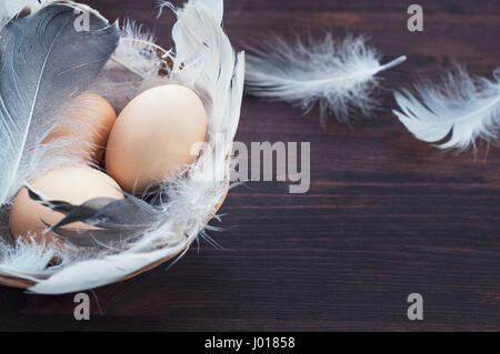 Three chicken eggs in a basket with feathers, selective focus, empty space on the right - Stock Photo