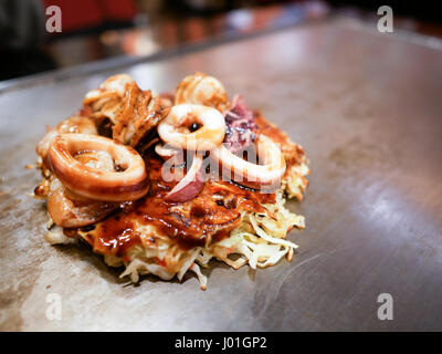 Seafood Okonomiyaki aka Japanese pizza on Tepanyaki pan. - Stock Photo