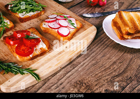 Four sandwiches with fresh vegetables, tomatoes, cucumbers, radish and arugula on a wooden background. Homemade - Stock Photo