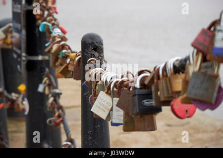 love locks attached to the fence at albert dock Liverpool UK - Stock Photo