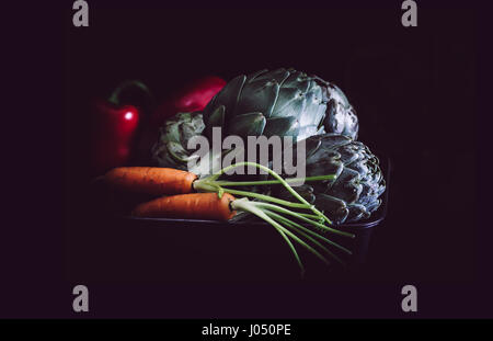 Carrots, artichokes and red peppers on black background. - Stock Photo