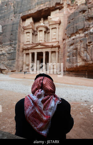 A Bedouin man sitting by the Treasury rock carved tomb in the ancient city of Petra, Jordan. - Stock Photo