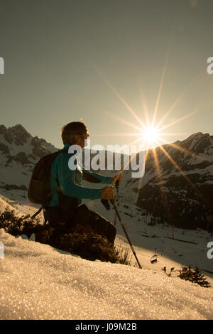 Nordic Walking as the sun sets hiking with backpack and poles rambler in the mountains and in the snow at sunset, - Stock Photo