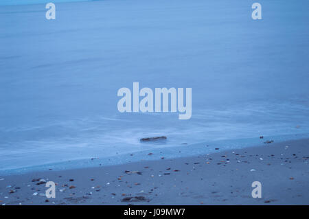 Blurry waves on beach shore. - Stock Photo