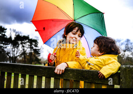 Overhead view of baby boy and brother in yellow anoraks with umbrella on park bench - Stock Photo