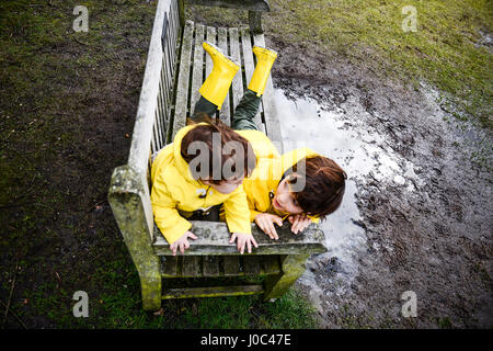 Overhead view of baby boy and brother in yellow anoraks on park bench - Stock Photo