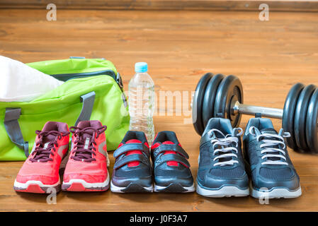 Sneakers for the whole family for sports on the wooden floor - Stock Photo