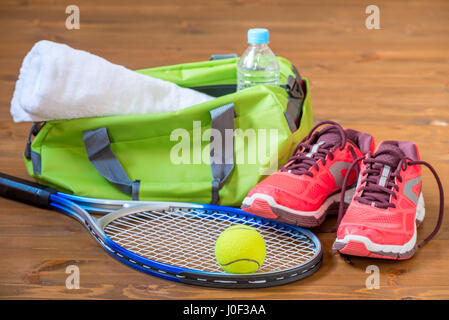 Accessories for playing tennis lie on the wooden dark floor - Stock Photo
