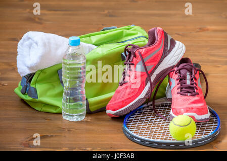 the composition of sports facilities on the dark wooden floor with a rocket for tennis - Stock Photo