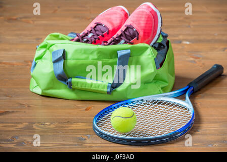 Racket and ball for tennis in focus on the background of bag with sneakers on the floor - Stock Photo