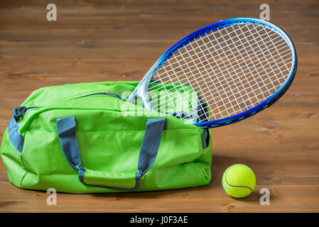 A tennis racket sticks out of a green sports bag, objects on the floor - Stock Photo