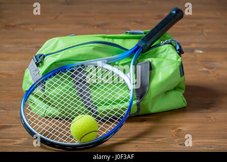 Green sports bag and a racket for a game of tennis close-up on the floor - Stock Photo