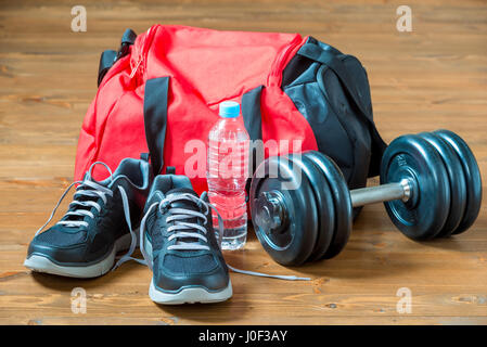 Red sports bag and sneakers near a heavy dumbbell on a wooden floor - Stock Photo