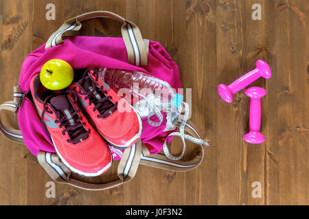 Women's sports bag with objects and clothes for a workout on a dark floor view from above - Stock Photo