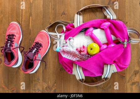 open sports bag and pink running shoes on a wooden floor top view - Stock Photo