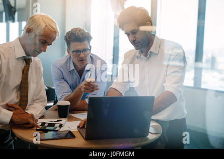 Business people talking while standing by table in office. Businessman giving demonstrating on laptop to colleagues - Stock Photo