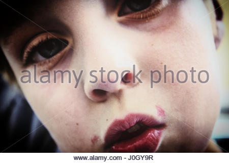Boys head in extreme close up with a strange look in his face - Stock Photo