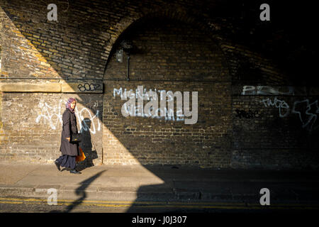 Asian woman walks past graffiti in London's Bethnal Green welcoming migrants. - Stock Photo