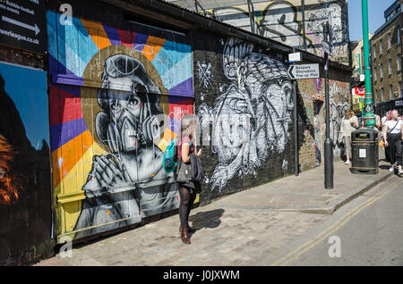 A woman stand in front of a wall which is covered in street art on Brick Lane in East London. - Stock Photo