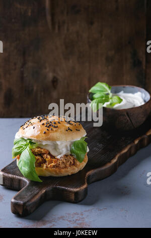 Homemade mini burger with pulled chicken, basil, mozzarella cheese and yogurt sauce on wooden serving board over - Stock Photo