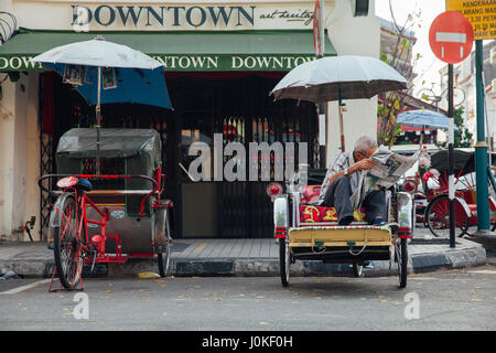 George Town, Malaysia - March 21, 2016: Rickshaw reading a newspaper sitting on the tricycle at the street of the - Stock Photo