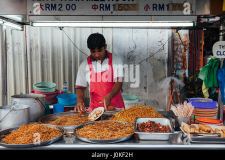 George Town,  Malaysia - March 22, 2016: Man sells kway teow noodles at the Kimberly Street Food Night Market on - Stock Photo