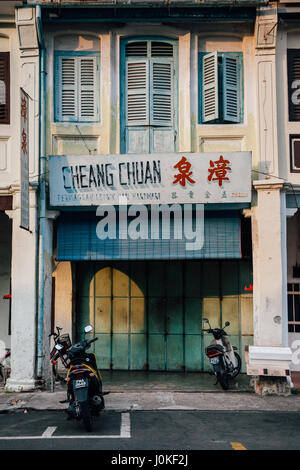 George Town,  Malaysia - March 22, 2016: Motorbikes parked near old shophouse building in UNESCO Heritage buffer - Stock Photo