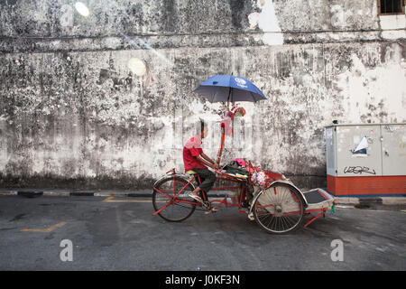 George Town,  Malaysia - March 21, 2016: Cycle rickshaw is riding down the street on March 21, 2016 in George Town, - Stock Photo