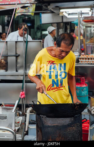 George Town,  Malaysia - March 22, 2016: Senior man cooks kway teow noodles in asian wok at the Kimberly Street - Stock Photo