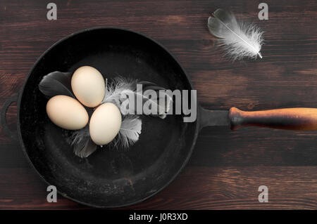 Three raw chicken eggs in a black cast-iron frying pan, top view - Stock Photo
