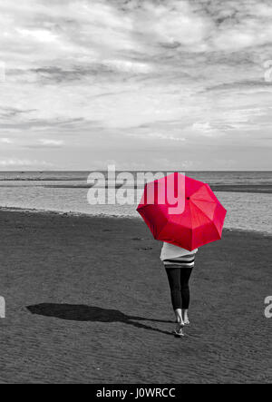 A woman walks on the beach with an open red umbrella. This photo is a color drop out with a conversion to grey scale - Stockfoto