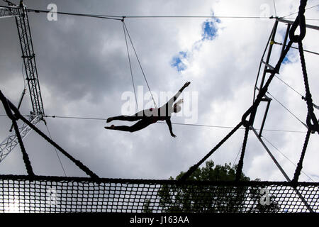 Trapeze studenst flying through the air. The Flying Trapeze School is situated in Regent's Park and run by the Gorilla - Stock Photo