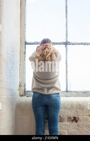 Rear view of a stressed blond woman standing by the window head in hands - Stock Photo