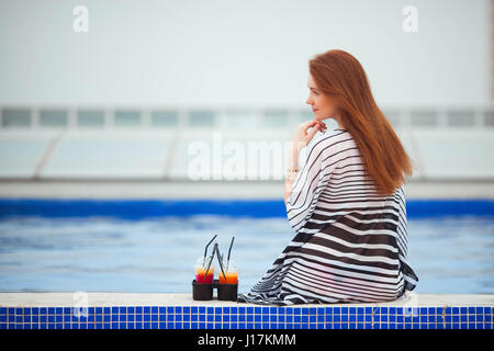 Beautiful red-haired girl in a striped pareo sits with his back to the camera by the pool. Next are the cocktails. - Stock Photo