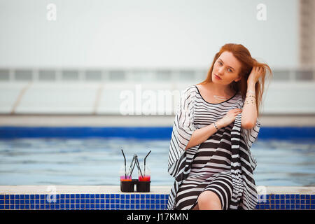 Beautiful red-haired girl in a striped pareo sits next to the pool. Next are the cocktails. - Stock Photo