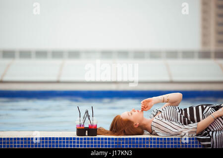 Beautiful red-haired girl in a striped pareo lying by the pool. Next are the cocktails. - Stock Photo
