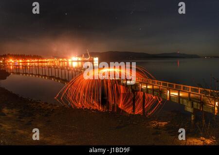 Spinning steel wool on bridge in Bellingham, WA - Stock Photo