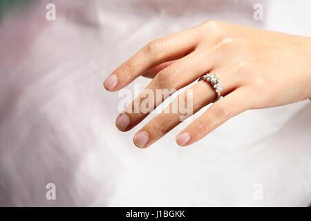 A woman hand wearing a diamond ring - Stock Photo