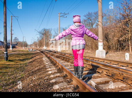 little girl in a red suit walking on rails on sunny spring day - Stock Photo